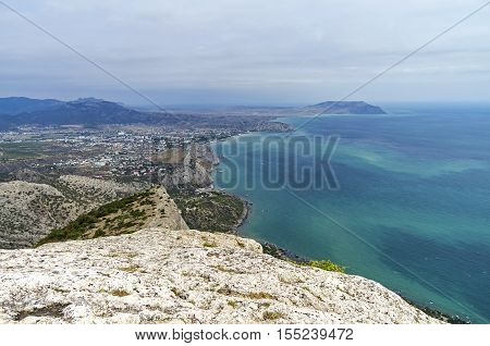 View from Mount Falcon on Sudak valley and the town of Sudak. Crimea September cloudy day.