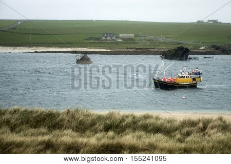 Orkney island Scotland scapa bay boat in front of sunken rusty ship wreck