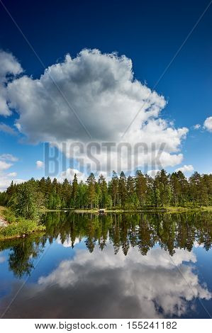 Relaxing Finnish landscape with lake forest trees sky and reflected clouds
