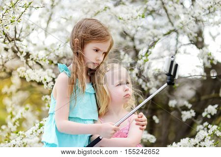Two Cute Little Sisters Taking A Photo Of Themself With A Selfie Stick
