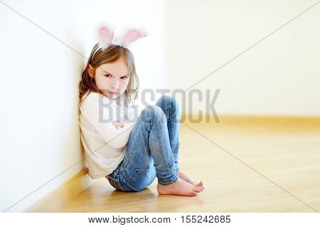 Very Angry Little Girl Wearing Bunny Ears Sitting On A Floor