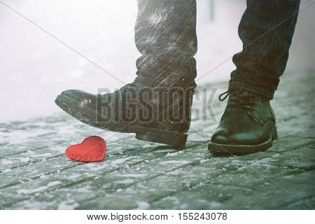 Tramples love. Symbol of separation. A man stepped on a shoe decorative heart. Color toning. The effect of old photos from scuffs and scratches
