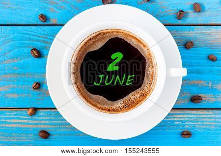 June 2nd. Day of the month 2 , everyday calendar written on morning coffee cup at blue wooden background. Summer concept, Top view.
