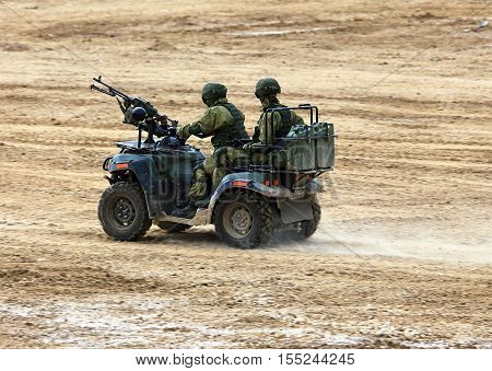 Two infantrymen armed with small arms on a march over rough terrain by a quad bike