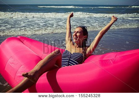 A dame rejoicing and smiling on a deep-rosy air rubber boat upping her hands wearing blue striped swimming suit, holding her sunglasses on the head, looking squinty on the sun.