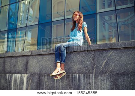 Positive Caucasian girl in sunglasses sitting on concrete bench and enjoying sunny day in the busy city