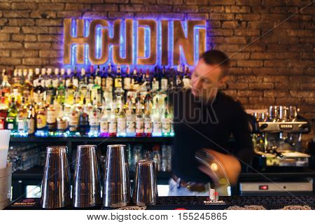 GRODNO BELARUS - NOV 7 2015: The bartender quickly working at a gastrobar HOUDINI in Grodno Belarus November 7 2015