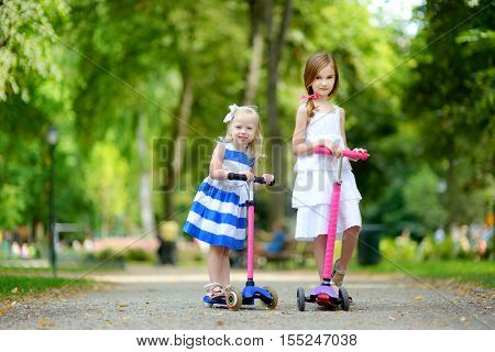 Two Adorable Little Sisters Wearing Beautiful Dresses Riding Their Scooters