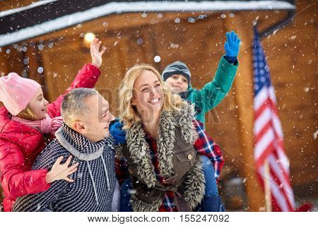 portrait young smiling family enjoying on snowy day