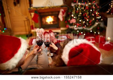 Toasting with glasses of red wine, back view