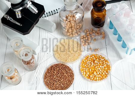 cereals in glass vials for analysis in laboratory with microscope wooden background no one