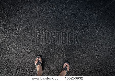 Top view of man feet with sandal on the road of asphalt.
