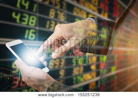 Businessman using smart phone mobile with display board of stock market quotes in background