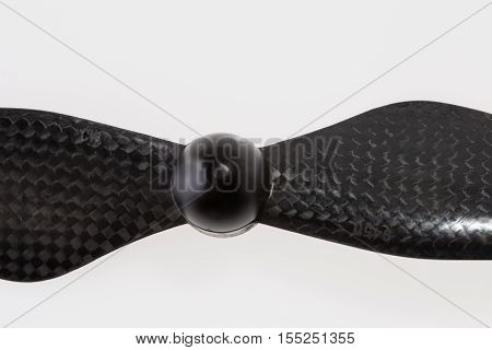 Close up of one carbon fiber self-tightening propeller for a quadcopter drone on white background. Size is 9450. This one is clockwise rotation direction. High angle view.