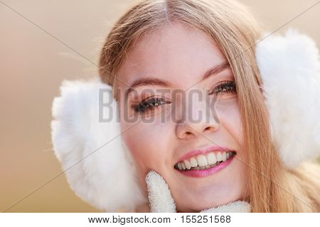 Portrait of pretty smiling fashionable woman in fall forest park. Happy gorgeous young girl in white earmuffs. Autumn winter fashion.