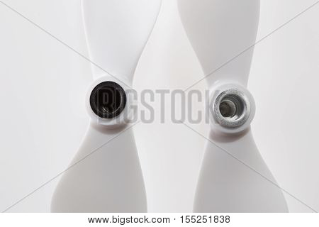 Set of two plastic self-tightening propellers for a quadcopter drone on white background. Size is 9450. One is clockwise and another one is counterclockwise rotation direction. Screw side. High angle view. poster