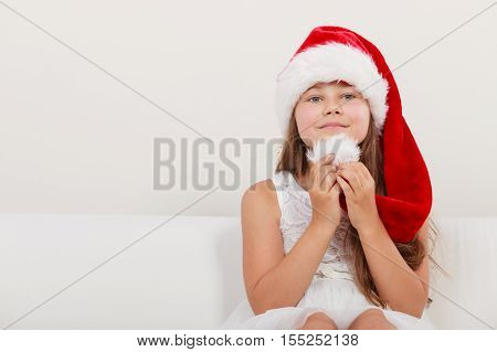 Cute little girl kid in red santa claus hat and white dress. Chrtistmas holiday season.
