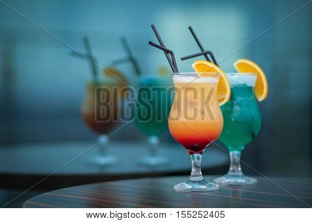blue and orange summer cocktails with straw; alcohol drinks with color ingredients and orange;