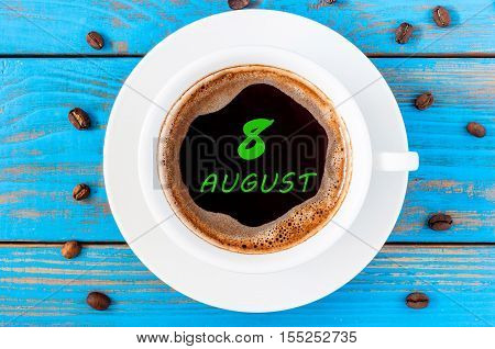 August 8th. Day 8 of month, morning coffee cup with calendar on drinks surface. Blue wooden background and beans. Top view. Summer time.