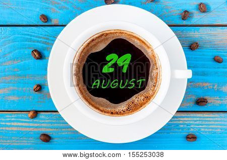 August 29th. Day 29 of month, morning coffee cup with calendar on drinks surface. Blue wooden background and beans. Top view. Summer time.