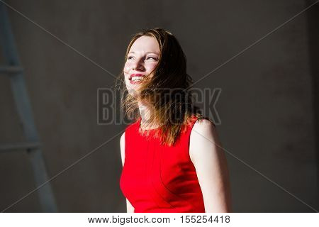 Smiling blonde in red dress with fluttering hair have fun at light room in sunny rays.