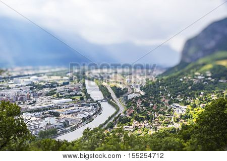 Grenoble city and Isere river France. Picturesque aerial view from Bastille in summer cloudy day. Tilt-shift Miniature Effect