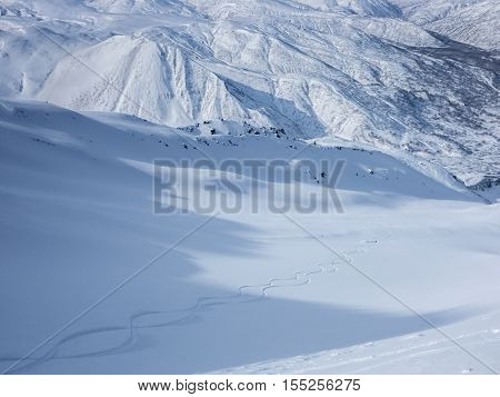 Skiers making two fresh tracks down a vast mountain valley in a snow covered landscape.