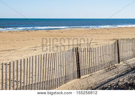 Picket fence on empty Sandbridge Beach in Virginia Beach, Virginia.