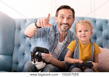 Spending time together. Handsome happy joyful man pointing at something and holding a game console while playing video games with his daughter