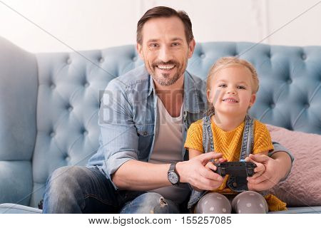 Having a great time. Nice optimistic caring father sitting hear his daughter and helping her with a game console while teaching her how to play video games