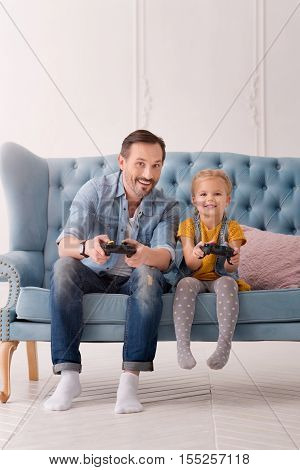 Time with children. Positive good looking caring father sitting next to his daughter and playing video games while spending time with his daughter