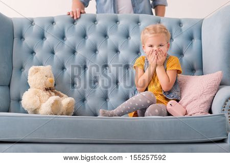 Keep silence. Cute beautiful blonde girl sitting on the couch and looking at you while covering her mouth with hands