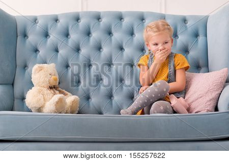Silence game. Pleasant adorable young girl sitting on the sofa and covering her mouth with a hand while playing in the silence game