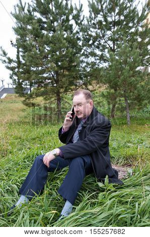 Man talking on the phone while sitting near the firs