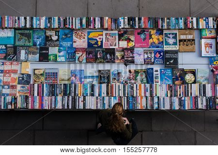 London, UK - October 22, 2016: A woman exploring used and second hand books and record bargains on London Thames Southbank.