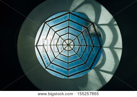 Spiderweb-shaped skylight with sunlight and an Islamic tower