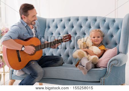 Music fan. Nice happy joyful man playing the guitar and laughing while singing for his daughter
