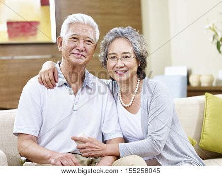 senior asian couple sitting on couch at home looking at camera smiling