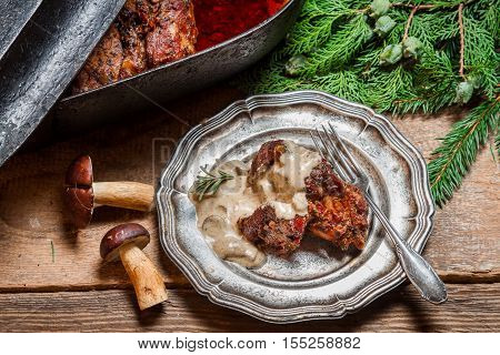 Venison served with wild mushroom sauce on old wooden table