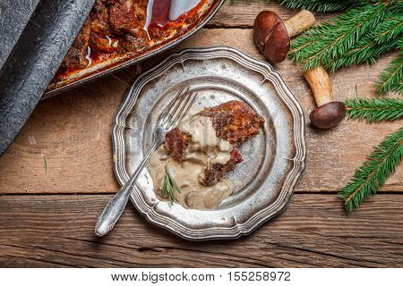 Venison prepared in a forest way on old wooden table