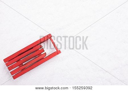 Top view of wooden red sled in the snow