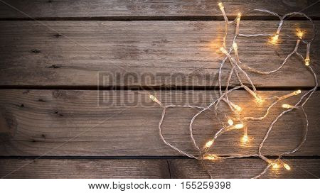 Christmas led lights on aged wooden bakground