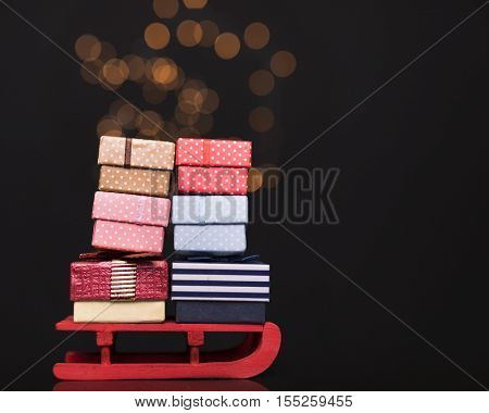 Red sled full of gift boxes on dark background