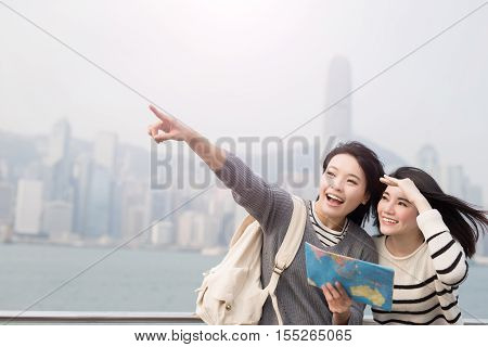 two beauty woman take map and show something in hongkong