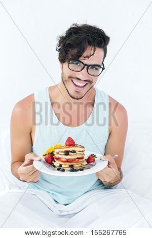 Young man having pancakes in bed