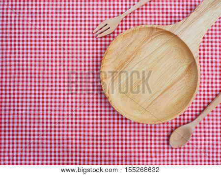 Empty plate with handle and spoons on red checked tablecloth. Top view.