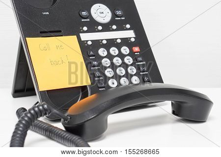 message of calling back on sticky note attach to IP phone