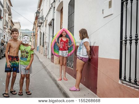 Xalo, Spain - August 21, 2016: Xalo street scene, Spanish children playing and acting up for camera in the narrow village street in which they live and play.