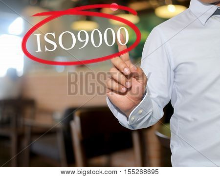 Hand of man touching text ISO9000 with white color on blur interior backgroundconcept of adoption to promote your business for organization.