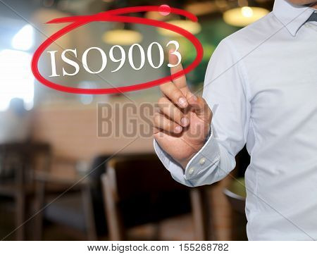 Hand of man touching text ISO9003 with white color on blur interior backgroundconcept of adoption to promote your business for organization.
